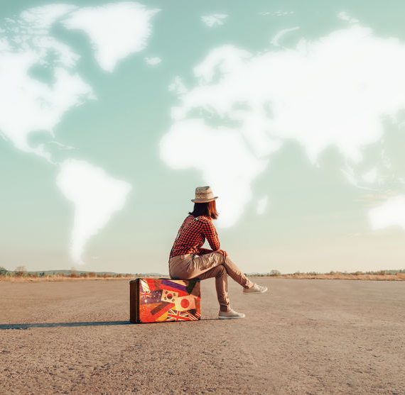 woman sitting on a suitcase and looking at clouds in a world map shape